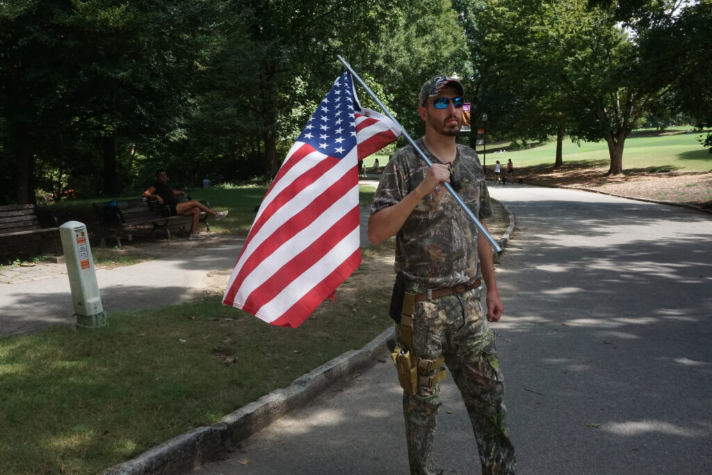 A three percent militia member wearing a full camo outfit, holding an American flag, and wearing a holstered pistol in Piedmont Park