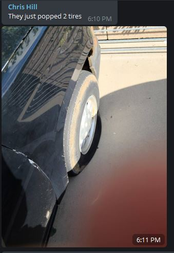"""A screenshot of Telegram chat showing a picture of a car with slashed tires and the text """"They just popped 2 tires"""""""